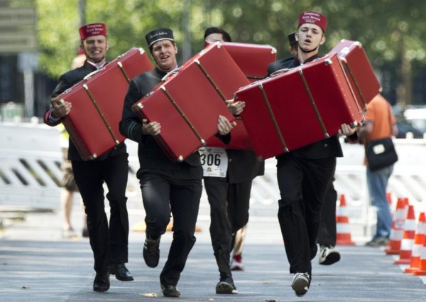 """Contestants in the porter event react as they carry a suitcase during the annual """"Berlin Waiters' Race"""" in Berlin, Germany on August 4, 2013. The competition features 6 categories, including fastest waitress, fastest porter and fastest cocktail mixer. AFP PHOTO / JOHN MACDOUGALL"""