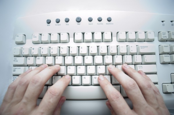 hands typing at a computer keyboard with a cross procesed colours